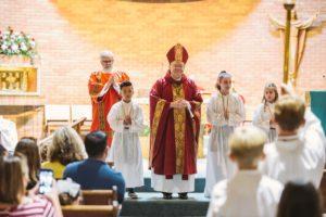 Deacon Alexander, Altar Server Dylan Nguyen, Bishop Kihneman, Altar Servers Olivia Myers and Julia Guice