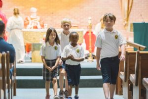 OLF students carry the gifts at the mass celebrated by Bishop Kihneman