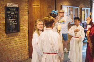 Julia Guice and fellow altar servers prepare for Bishop Kihneman mass