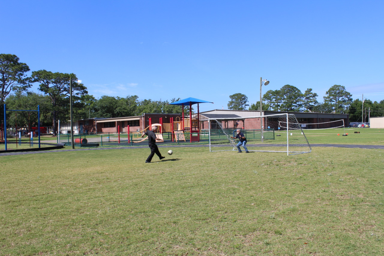 Father Henry scores the first goal on OLF's new soccer field.