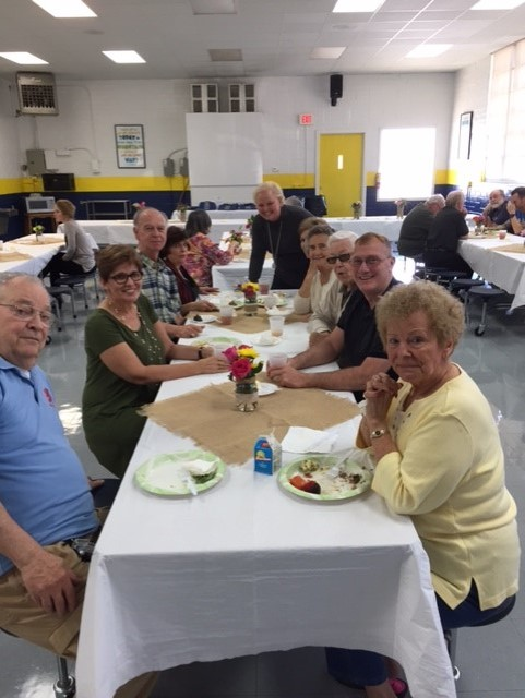 Volunteers enjoy the special lunch as part of National Catholic Schools Week